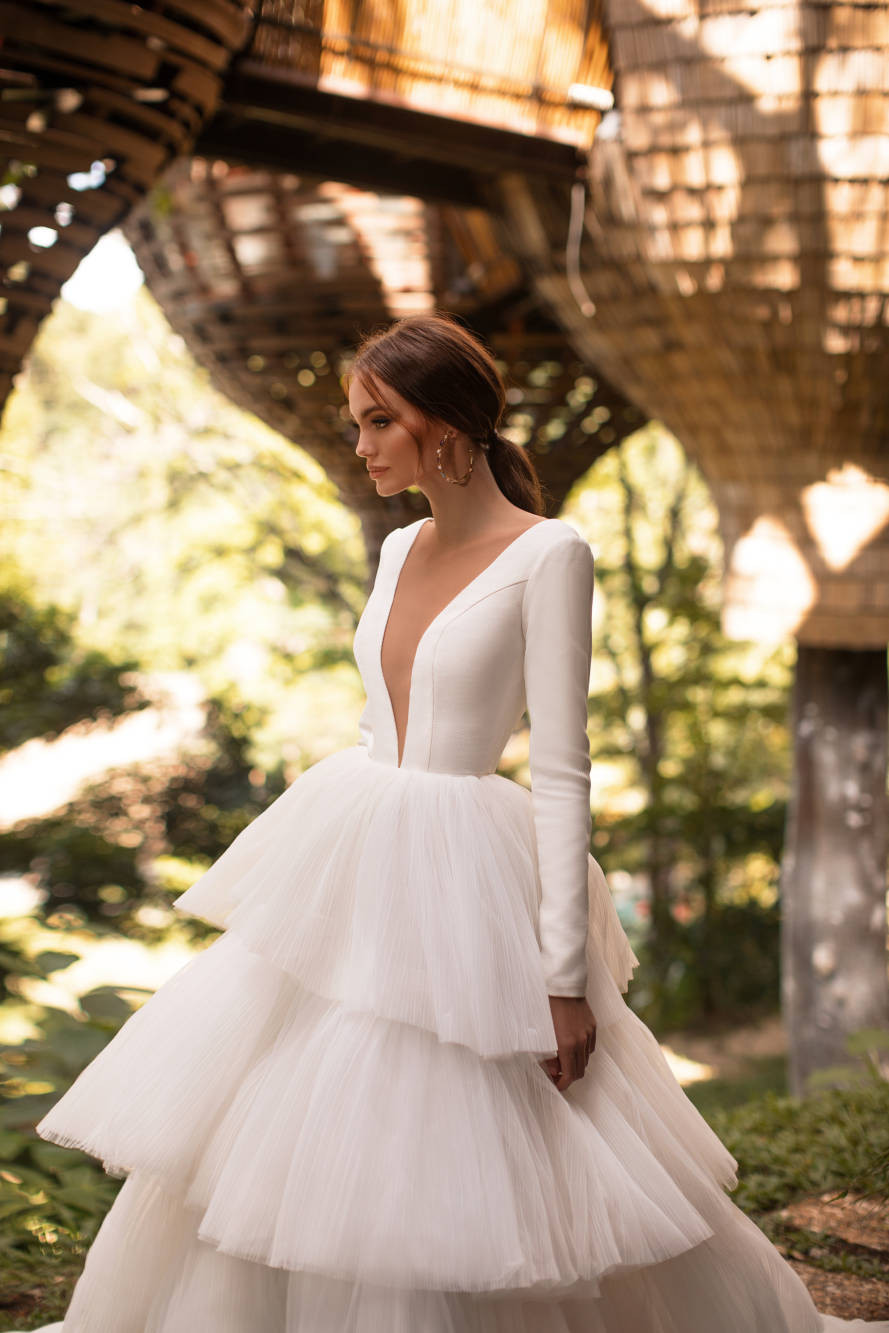 A Milla Nova ball gown wedding dress with a layered tulle skirt, long sleeves and a deep v neckline