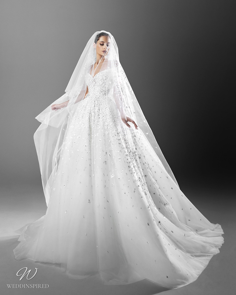 A Zuhair Murad ball gown off the shoulder princess wedding dress with crystals and a veil