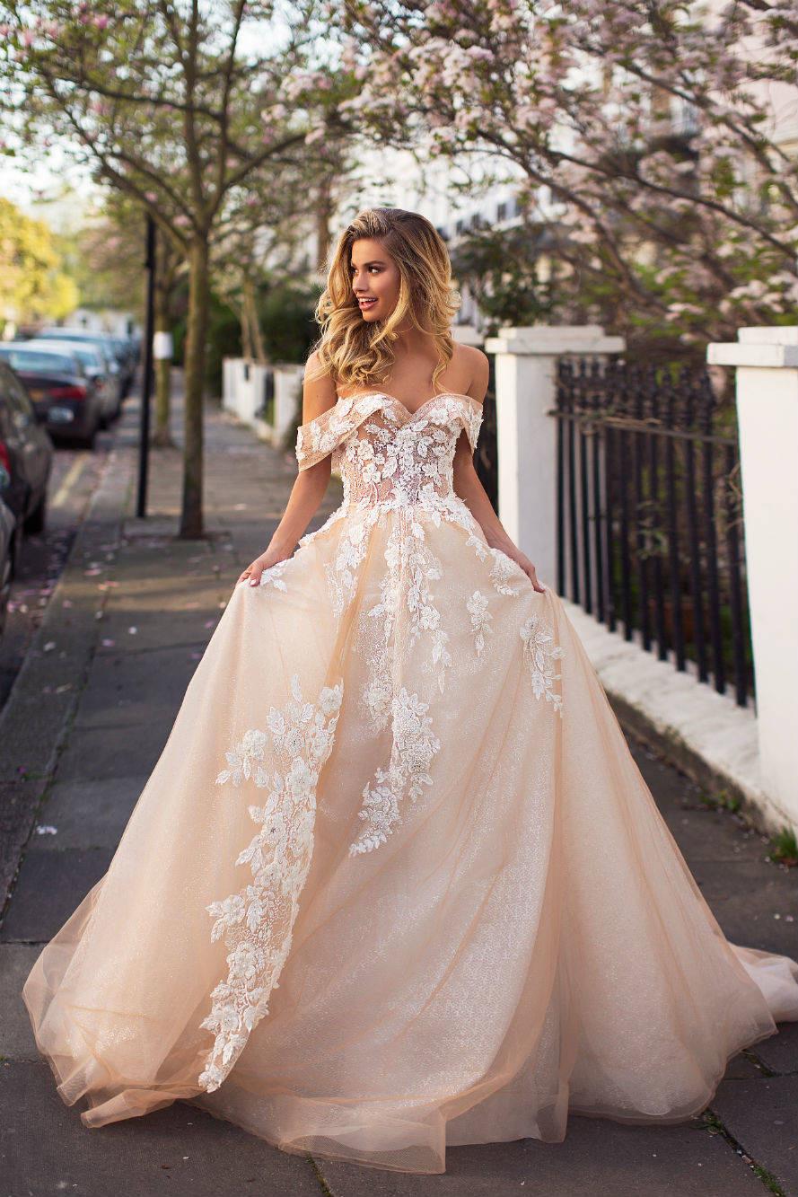 A Milla Nova off the shoulder blush lace romantic ball gown wedding dress