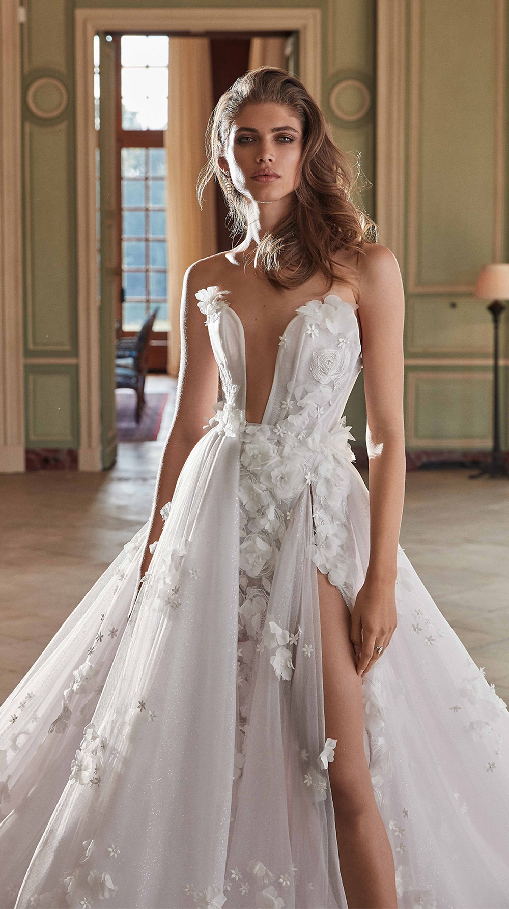Dripping with 3D petals and clear sparkle embellishments, this whimsical A-line wedding gown reflects a light lavender color through layers of silk and tulle with a sheer plunging corset, high slit, and romantic layered overskirt