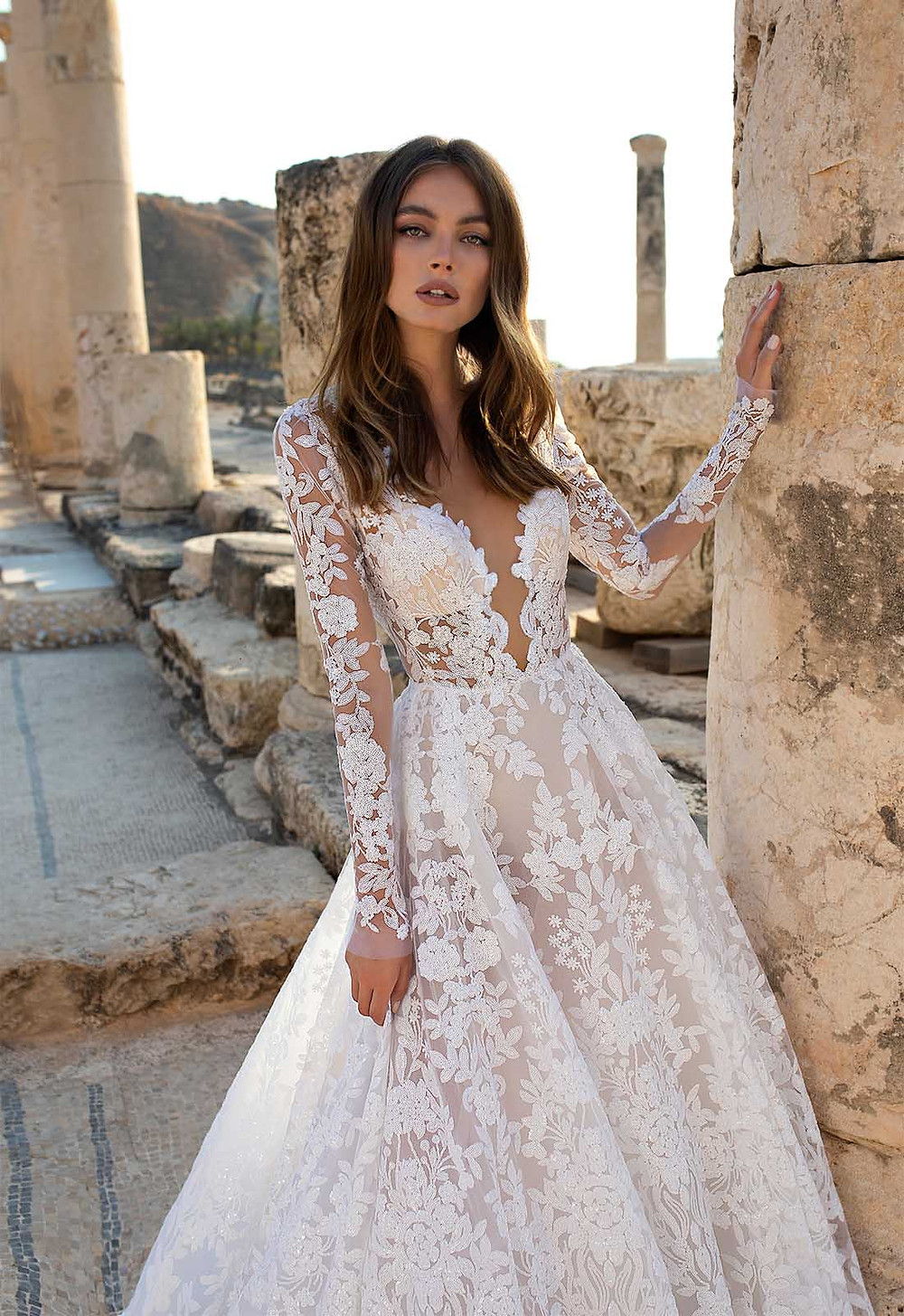A Pnina Tornai lace ball gown wedding dress with long sleeves and a v neckline