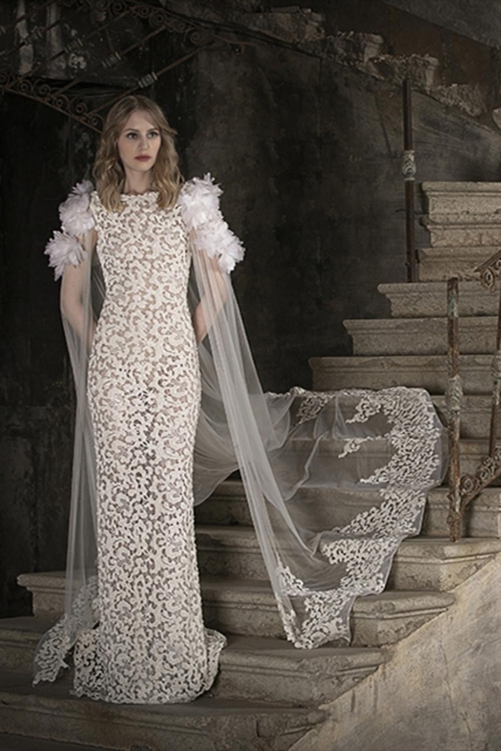 A sleek cut macramé wedding dress, featuring a tulle cape and statement ruffles on the shoulder