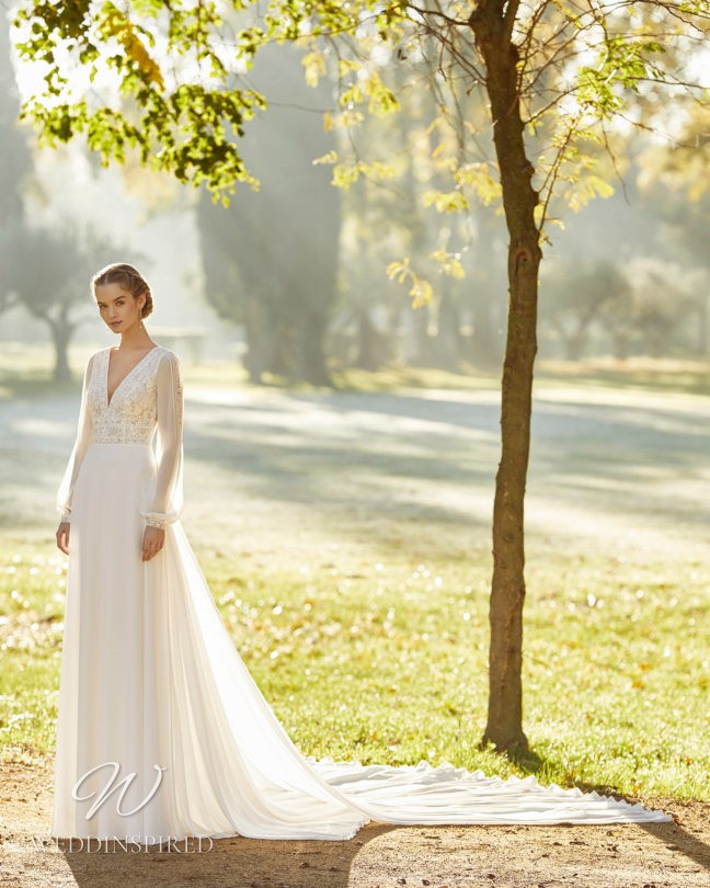 An Aire Barcelona 2021 flowy A-line wedding dress with long sleeves and a v neck