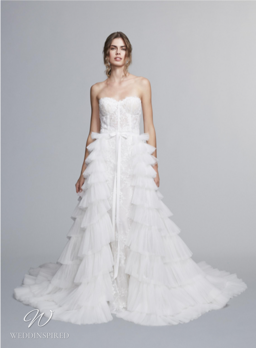 A Marchesa Notte Fall 2021 strapless lace mermaid wedding dress with a ruffle tulle detachable skirt