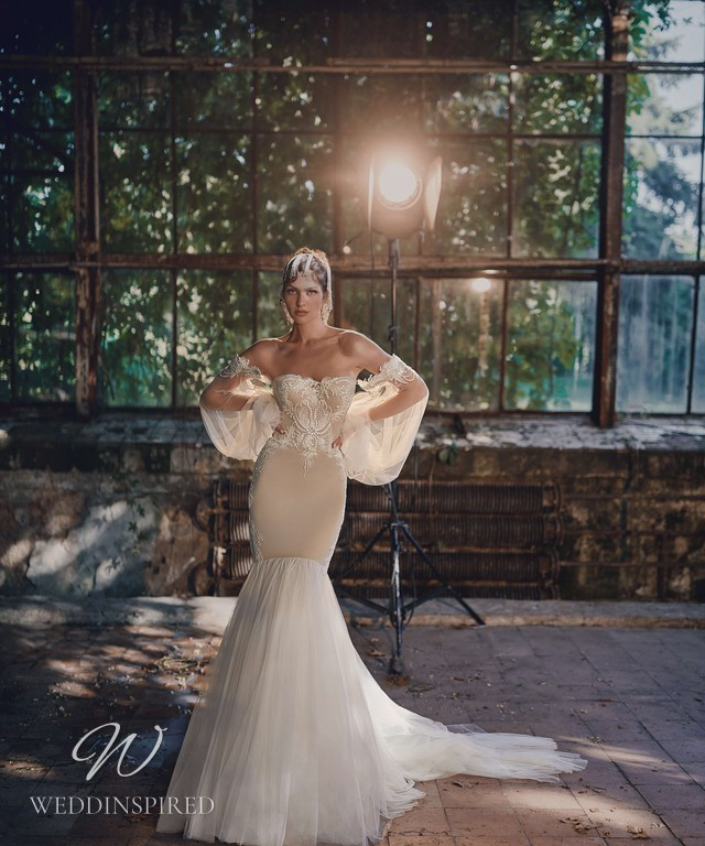An Ange Etoiles 2021 off the shoulder tan and beige boho lace and tulle mermaid wedding dress with long sleeves
