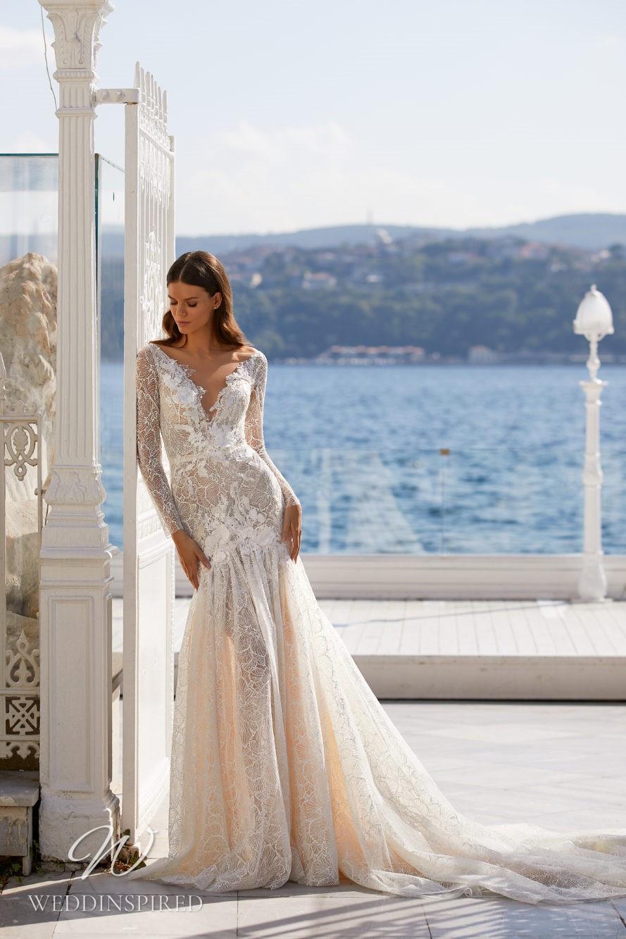 A Milla Nova 2021 blush lace mermaid wedding dress with long sleeves and a v neck
