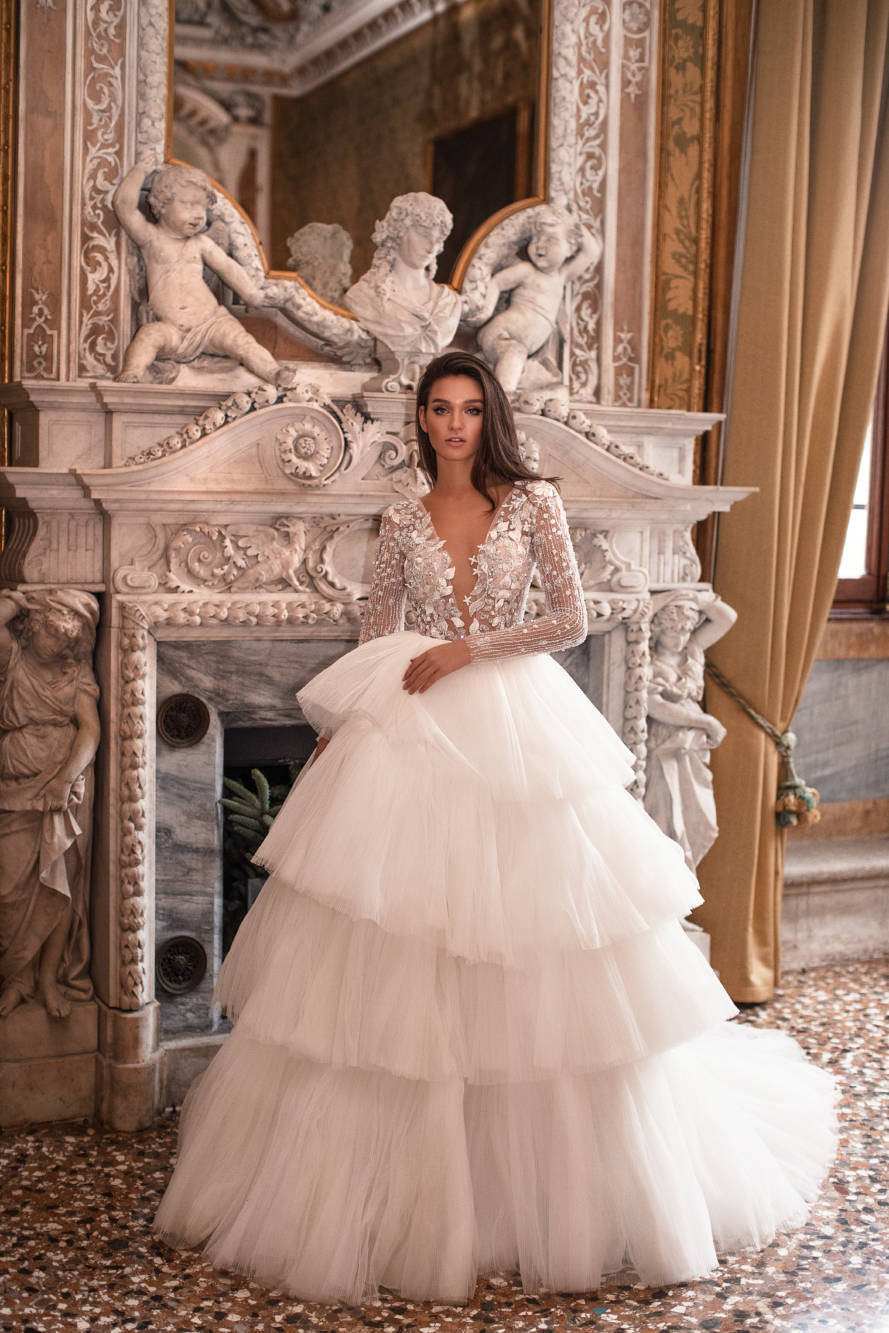 A Milla Nova ball gown wedding dress with a layered tulle skirt, lace, long sleeves, a deep v neckline and crystals
