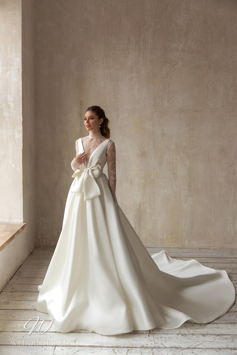 An Eva Lendel 2021 lace and silk ball gown wedding dress with long sleeves and a train