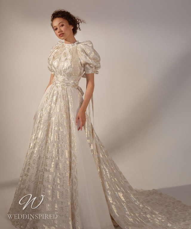 A Rara Avis 2021 modest gold and white ball gown wedding dress with a high neck and short balloon sleeves