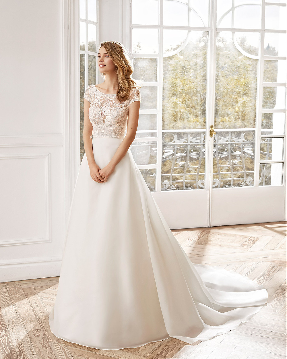 An Aire Barcelona 2020 lace and chiffon A-line wedding dress with cap sleeves and a high neckline