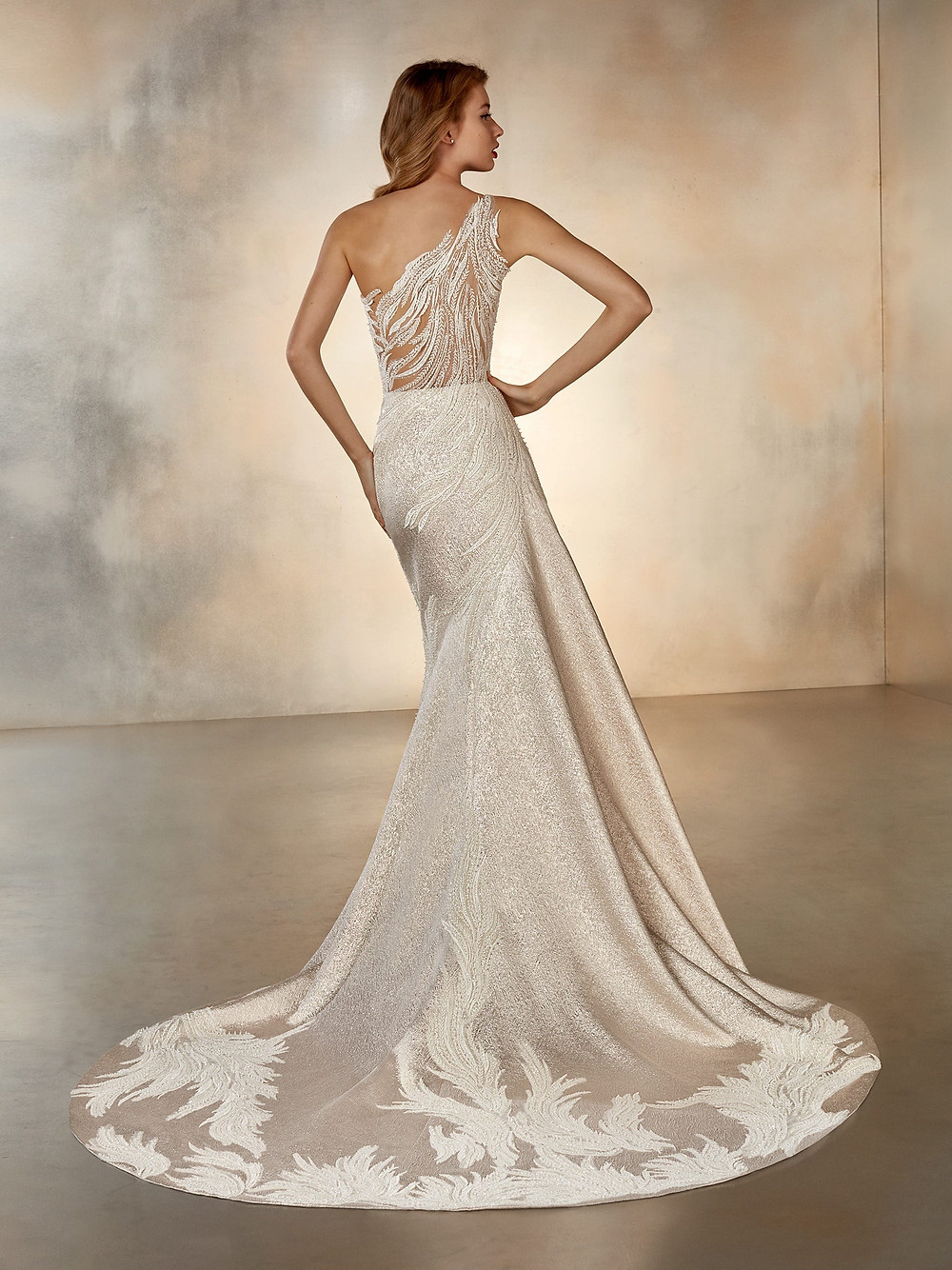 A champagne color one shoulder wedding dress with plenty of sparkle and shine and floral embellishments