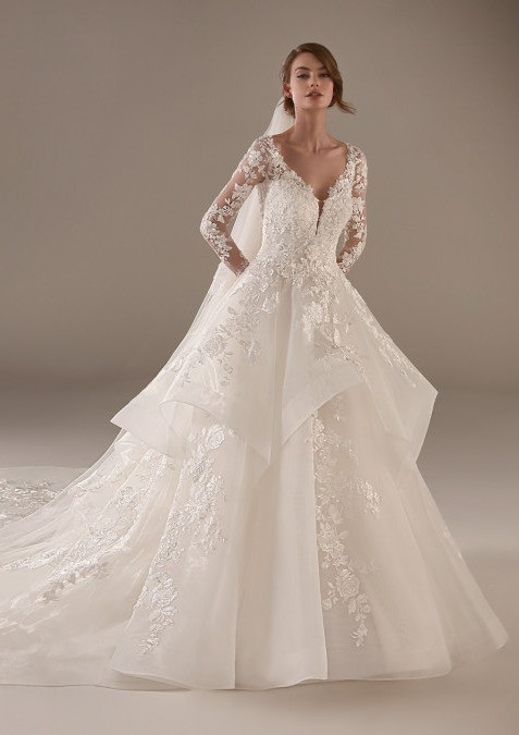A Pronovias lace ball gown wedding dress with a layered skirt and long sleeves