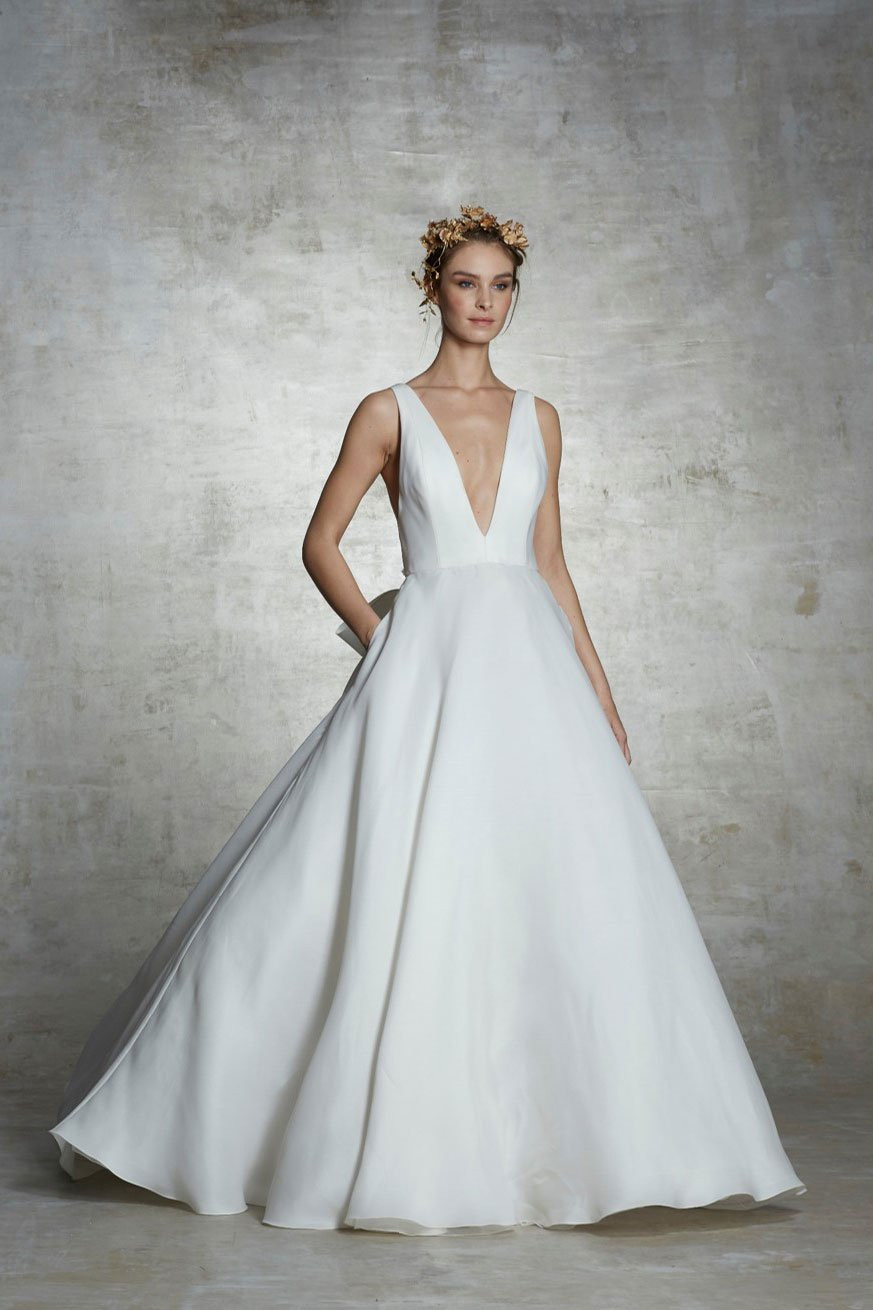 A Marchesa simple crepe ball gown wedding dress with pockets and a v neckline