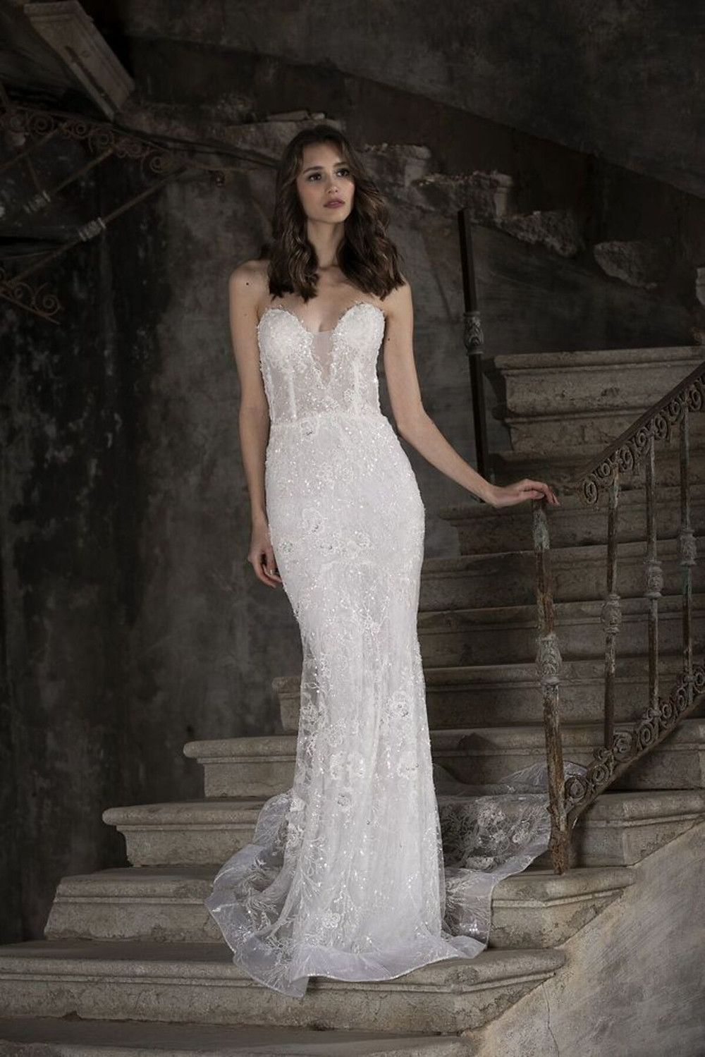 A mermaid wedding dress featuring lace embroidered with sequins and a corseted bust