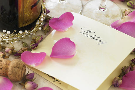 Wedding invitation next to champagne bottle surrounded by flower petals.jpg