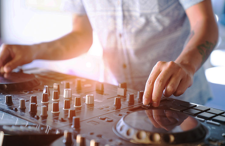 Dj mixing outdoor at beach party festival with crowd of people in background.jpg