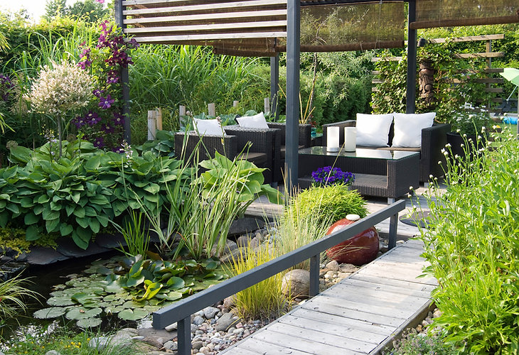 A modern furnished patio and pergola with a small pond.jpg