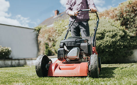 Man mowing the grass with a manual petrol lawnmower..jpg