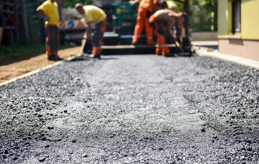 Team of Workers making and constructing asphalt road construction with finisher.jpg