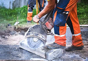 Construction worker cutting concrete paving stabs.jpg