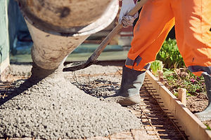 Worker with gum boots spreading ready mix concrete.jpg