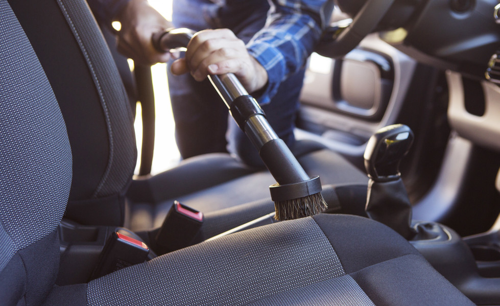 Man Hoovering Seat Of Car During Car Cle