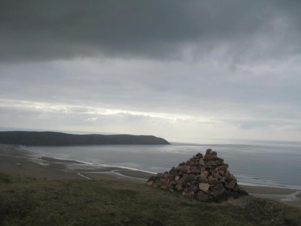 A Cairn overlooking Woolacombe Bay from the headland above in stormier weather