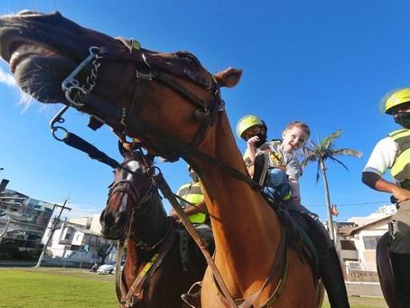 Menino com autismo se encanta com cavalos da Brigada Militar em Torres, Litoral Norte do RS.