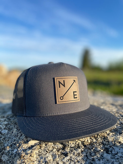 Nor'easter Apparel Trucker Hat in charcoal with black mesh back decorated with compass design, front view.