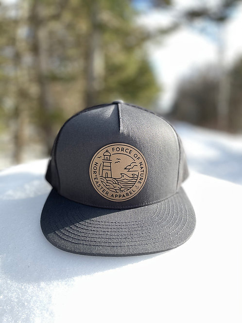 Nor'easter Apparel Trucker hat front view in black and charcoal sitting on snow