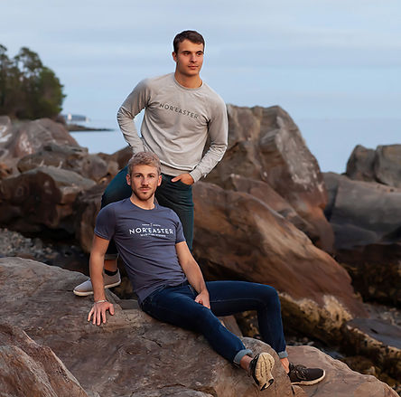 Noreaster-apparel-mens-french terry crew neck sweater in heather grey and mens signature tri-blend cotton tshirt in heather navy, worn by men sitting on rocks at Point Pleasant Park in Halifax