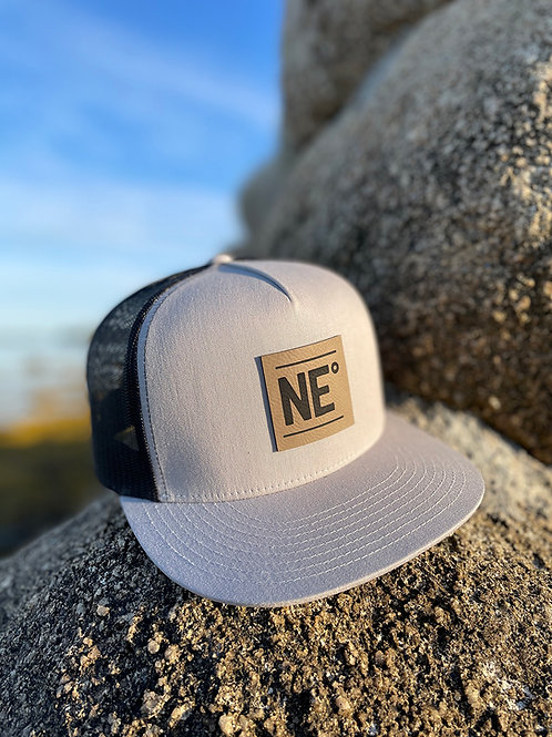 Nor'easter Apparel Trucker Hat in light grey with black mesh back decorated with NE° logo, side view.