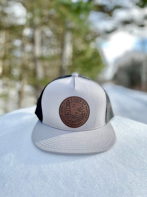 Nor'easter Apparel Trucker hat in light grey and black front view sitting on snow