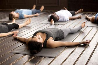 Des personnes allongées sur le sol en yoga nidra
