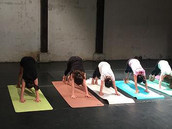 cours collectif de Yoga pour les enfants, cinq enfants en posture du chien tête en bas