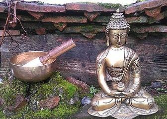 un bol tibetain et une statue de bouddha