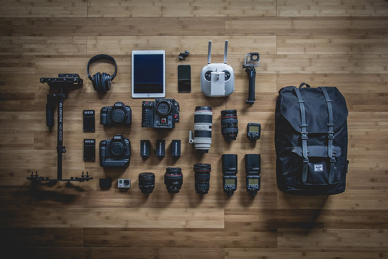 Several dslr camera bodies, seperate lenses of different sizes, headphones, tripod, Go Pro case and mount, Go Pro camera, several flashes, cellphone, tablet, and backpack. All items are laid out on the florr.