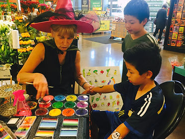 Artist, Jacqueline Knapp with two brothers who requested both arms painted at Los Altos Whole Foods Market on Halloween, 2017. They are intently watching what she is creating.