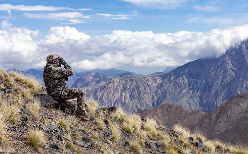 Man in camouflage on the slope is watching through binoculars in the mountains. Hunter loo