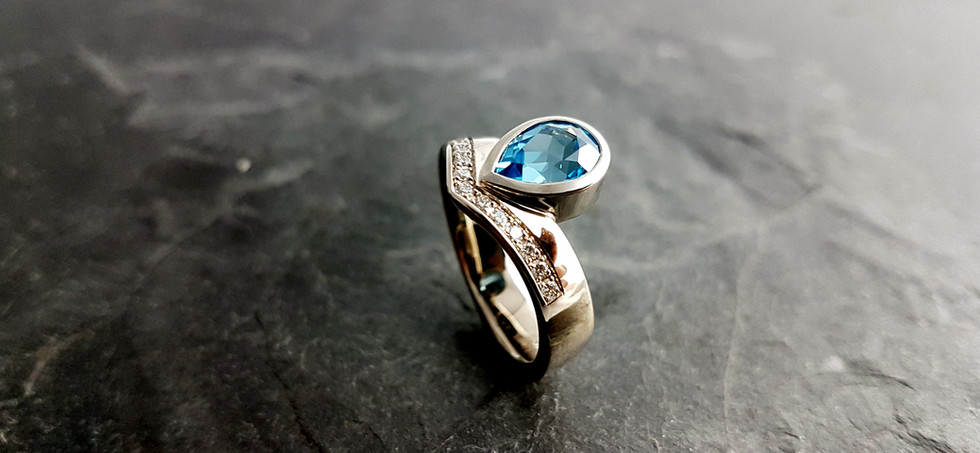 Ring aus 585/- Weißgold mit einem blauen Topas und Brillanten im Verschnitt gefasst