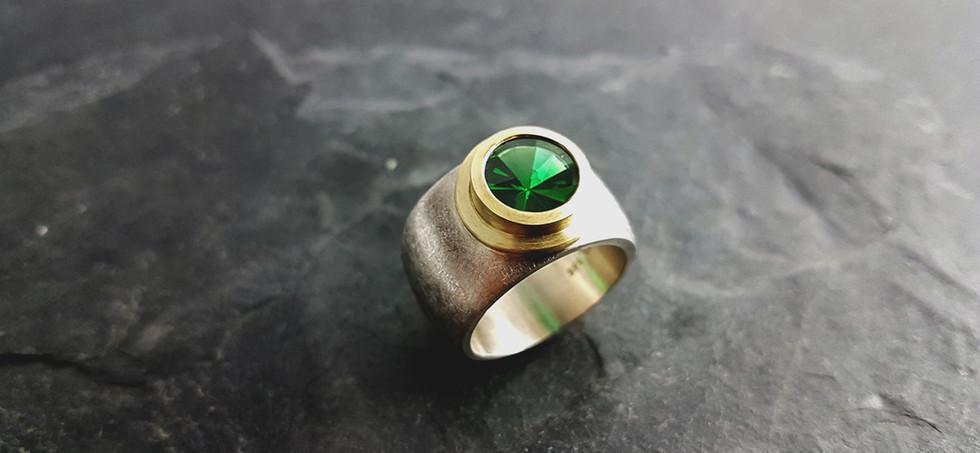 Ring aus 585/- Gelbgold und 925/- Silber mit synth. grünen Spinell