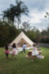 Kids playing in backyard with bell tent