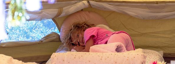 Girl on bed in glamping tent