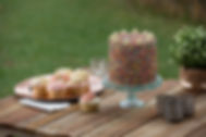 100s & 1000s cake with cupcakes on a wooden table