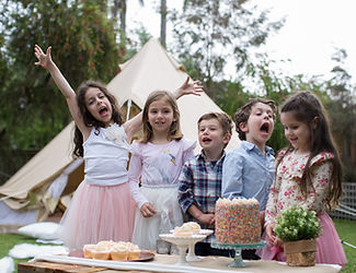 Kids with cake at backyard glamping party