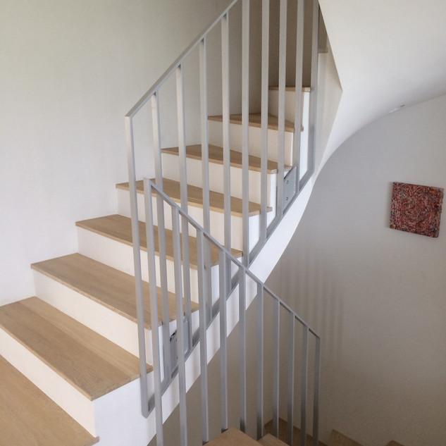 Holztreppe mit Geländer aus Metall