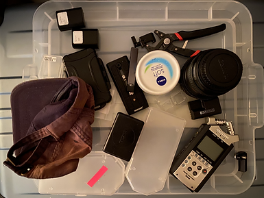 A plastic transparent tray with items messily laid out on top of it: a baseball cap, some  camera batteries, a zoom H4N audio recorder, canon lens, an adjustable wrench, a tripod plate, a juul e-cigarette and a large pot of Nivea soft moisturiser.