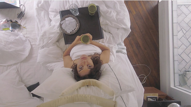 A birds eye photo of Kyla in bed looking directly into the camera. On her lap is a lap tray, with a myriad of green juices.