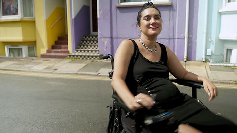 In front of bright pastel coloured houses, a sun kissed Kyla, a mixed heritage woman in her 30s, spins in her power chair and she wears red lipstick, a thick chain necklace and a black dress. Although dynamic and mid-spin, she is relaxed but gleeful.