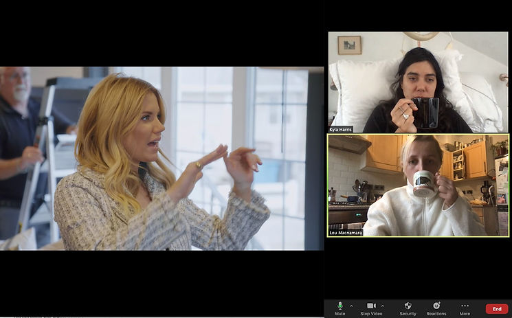 A Zoom screen showing a still of Dream Home Makeover. In one screen Kyla, is in bed holding a Black mug up to her mouth. The screen below shows Lou in her kitchen. Lou holds a white and black mug up to her mouth in unison.